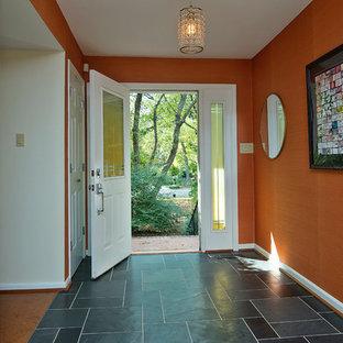 Immagine di un ingresso minimalista di medie dimensioni con pareti arancioni, pavimento in sughero, una porta singola, una porta bianca e pavimento beige
