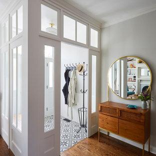 Klassischer Eingang mit Vestibül, weißer Wandfarbe, dunklem Holzboden, weißer Tür und braunem Boden in Chicago
