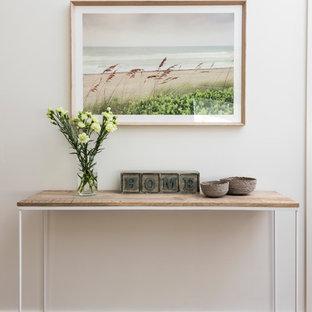 На фото: прихожая среднего размера в морском стиле с белыми стенами, полом из бамбука, коричневым полом и входной дверью из дерева среднего тона
