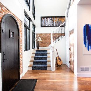Esempio di un ingresso chic con pareti bianche, pavimento in legno massello medio, una porta singola, una porta nera, pavimento marrone e pareti in mattoni