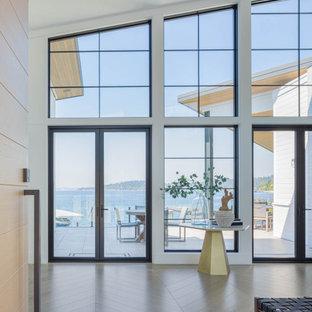 Неиссякаемый источник вдохновения для домашнего уюта: фойе в морском стиле с белыми стенами, светлым паркетным полом, одностворчатой входной дверью, входной дверью из светлого дерева и сводчатым потолком