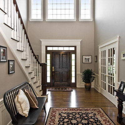 Inspiration for a timeless dark wood floor and brown floor entryway remodel in New York with a dark wood front door and beige walls
