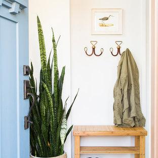 Imagen de puerta principal costera con paredes blancas, suelo de madera en tonos medios, puerta simple, puerta azul y suelo gris