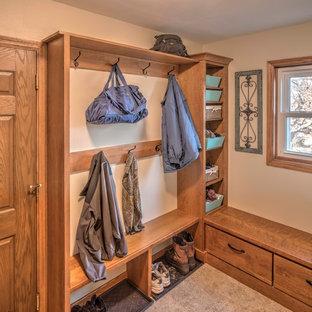 Idéer för mellanstora amerikanska kapprum, med klinkergolv i keramik, beige väggar, en enkeldörr och mellanmörk trädörr
