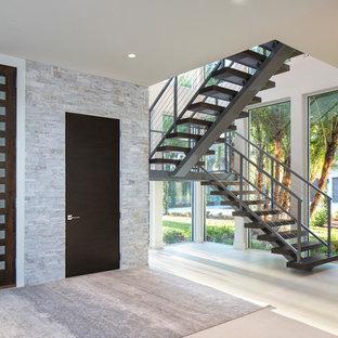Foto på en stor funkis ingång och ytterdörr, med grå väggar, ljust trägolv, en enkeldörr och mörk trädörr