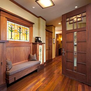 Amerikansk inredning av en entré, med beige väggar, mellanmörkt trägolv, en enkeldörr och mörk trädörr