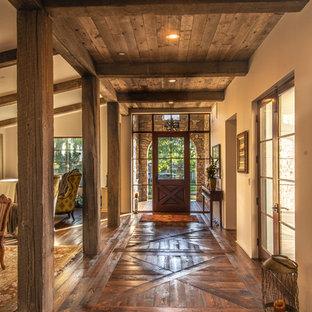 Inspiration for a rustic entrance in Los Angeles with beige walls, dark hardwood flooring, a single front door, a dark wood front door and brown floors.
