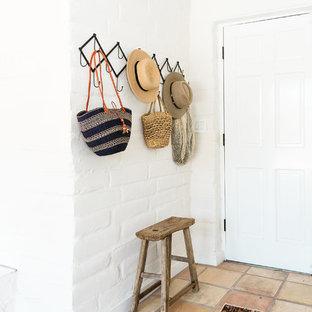 Esempio di un ingresso o corridoio american style con pareti bianche, pavimento in terracotta, una porta singola e una porta bianca