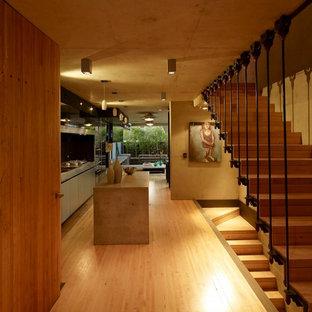 Diseño de distribuidor industrial, pequeño, con paredes marrones, suelo de madera clara, puerta simple, puerta de madera en tonos medios y suelo beige