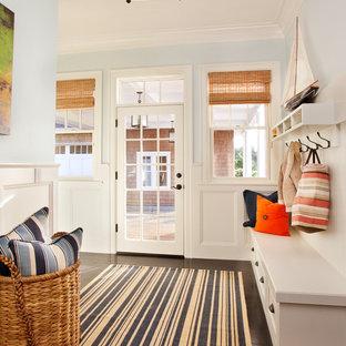 Idée de décoration pour une grande entrée marine avec un vestiaire, un mur bleu, une porte simple, une porte en verre et un sol en bois foncé.