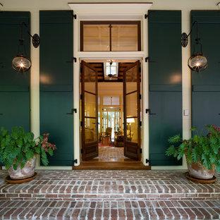 Idee per una porta d'ingresso chic con una porta a due ante, una porta in vetro e pavimento in mattoni