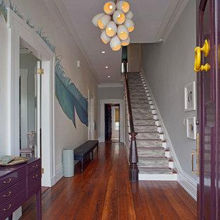 アトランタの中サイズの片開きドアエクレクティックスタイルのおしゃれな玄関ロビー (グレーの壁、無垢フローリング、紫のドア、茶色い床) の写真