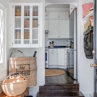 На фото: маленький тамбур в стиле шебби-шик с белыми стенами, паркетным полом среднего тона, одностворчатой входной дверью, черной входной дверью и коричневым полом с