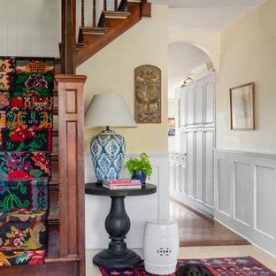 Ispirazione per un ingresso bohémian di medie dimensioni con pareti gialle, pavimento in pietra calcarea, una porta singola, una porta bianca, pavimento giallo e boiserie