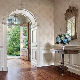 Großer Klassischer Eingang mit Foyer, beiger Wandfarbe, dunklem Holzboden, Einzeltür, hellbrauner Holztür und braunem Boden in New York