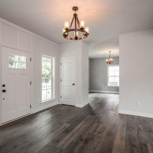 На фото: входная дверь в классическом стиле с белыми стенами, паркетным полом среднего тона, одностворчатой входной дверью, белой входной дверью, коричневым полом и панелями на стенах