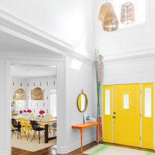 Modelo de distribuidor actual, grande, con paredes blancas, suelo de madera en tonos medios, puerta simple y puerta amarilla
