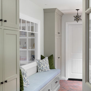 Large cottage brick floor and red floor mudroom photo in Boston with gray walls
