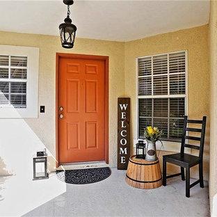 他の地域の片開きドアエクレクティックスタイルのおしゃれな玄関 (ベージュの壁、コンクリートの床、オレンジのドア、グレーの床) の写真