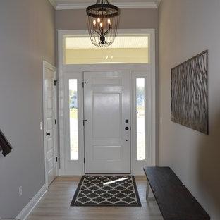 Cette photo montre un hall d'entrée chic de taille moyenne avec un mur beige, un sol en vinyl, une porte simple, une porte blanche et un sol beige.