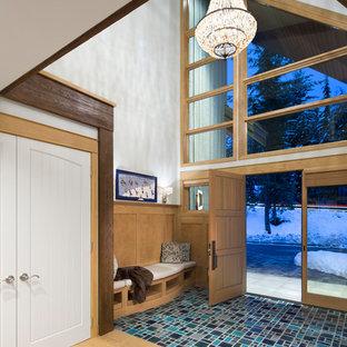 他の地域の中くらいの片開きドアラスティックスタイルのおしゃれな玄関ロビー (木目調のドア、ターコイズの床、グレーの壁、セラミックタイルの床) の写真