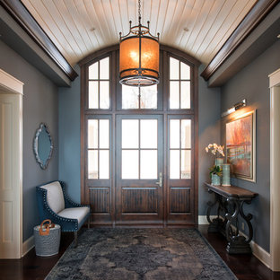 Example of a large classic dark wood floor and brown floor entryway design in Minneapolis with blue walls and a dark wood front door