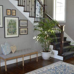 Cette photo montre une petite entrée craftsman avec un mur gris et un sol en bois brun.