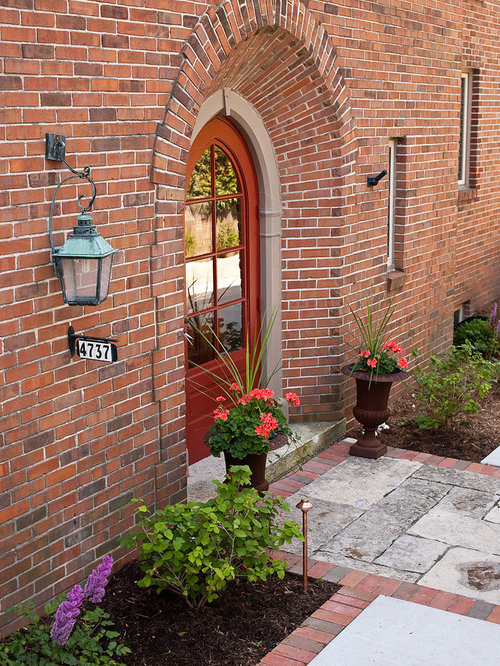 inspiration for a mid sized timeless entryway remodel in milwaukee with a red front door