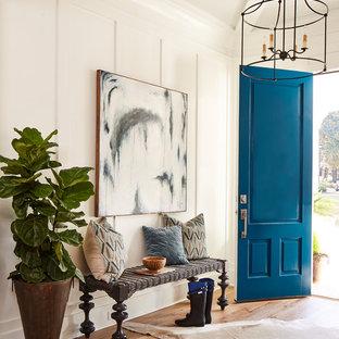 Réalisation d'une entrée champêtre avec un couloir, un mur blanc, un sol en bois brun, une porte bleue et un sol marron.