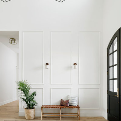 Example of a large transitional light wood floor and beige floor entryway design in Phoenix with white walls and a black front door