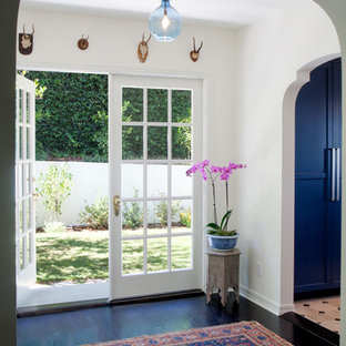 Example of a mid-sized tuscan dark wood floor and black floor entryway design in Los Angeles with white walls and a glass front door