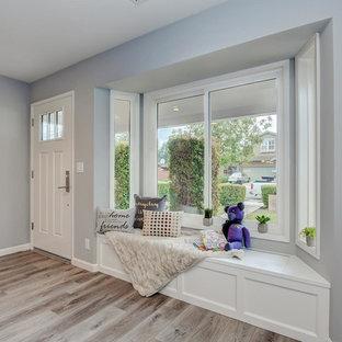 Идея дизайна: большое фойе со шкафом для обуви в современном стиле с серыми стенами, полом из керамической плитки, поворотной входной дверью, белой входной дверью и серым полом