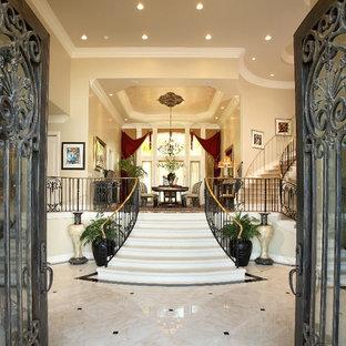 Пример оригинального дизайна: огромное фойе в классическом стиле с бежевыми стенами, мраморным полом, двустворчатой входной дверью, металлической входной дверью и бежевым полом