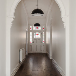 This is an example of a transitional entry hall in Melbourne with white walls, medium hardwood floors, a single front door, a white front door and brown floor.