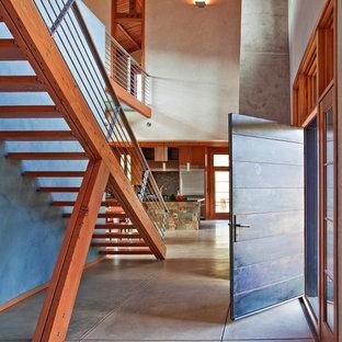 Inredning av en industriell mellanstor ingång och ytterdörr, med betonggolv, grått golv, en enkeldörr, metalldörr och vita väggar