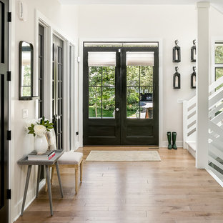Inspiration for a country foyer in Chicago with white walls, a double front door, a black front door and brown floor.