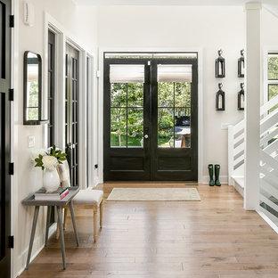 Ejemplo de distribuidor campestre con paredes blancas, puerta doble, puerta negra y suelo marrón