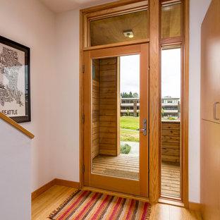シアトルの中くらいの片開きドアモダンスタイルのおしゃれな玄関ロビー (白い壁、竹フローリング、ガラスドア) の写真