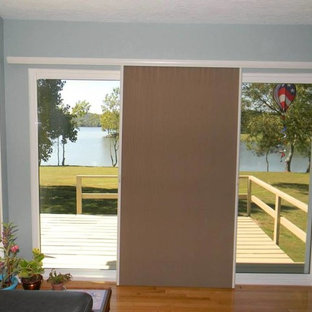 Large trendy medium tone wood floor entryway photo in Other with blue walls and a glass front door
