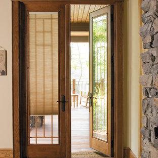 Ispirazione per un ingresso design di medie dimensioni con pareti beige, una porta a due ante e una porta in legno chiaro