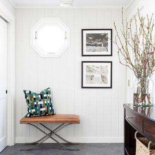 Example of a beach style porcelain tile and gray floor foyer design in Boston with white walls