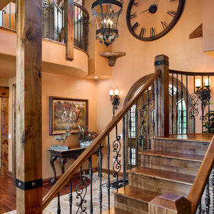 Mid-sized mountain style medium tone wood floor and brown floor entryway photo in Milwaukee with orange walls and a dark wood front door