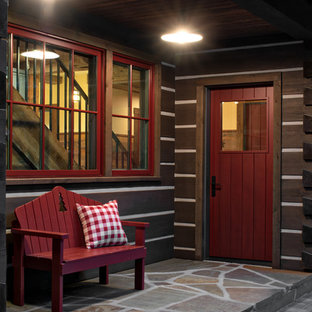 Bild på en rustik ingång och ytterdörr, med bruna väggar, en enkeldörr, en röd dörr och grått golv