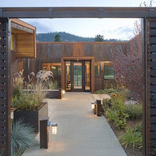 シアトルの大きい片開きドアコンテンポラリースタイルのおしゃれな玄関 (ガラスドア、コンクリートの床) の写真