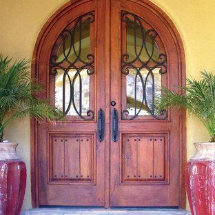 フェニックスの中くらいの両開きドアラスティックスタイルのおしゃれな玄関ドア (黄色い壁、テラコッタタイルの床、木目調のドア) の写真
