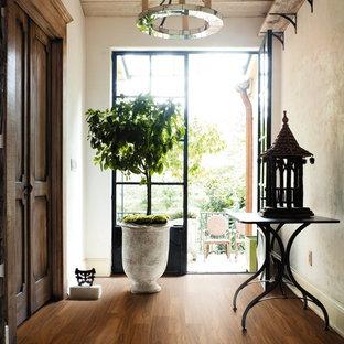 На фото: узкая прихожая среднего размера с бежевыми стенами, паркетным полом среднего тона, двустворчатой входной дверью и черной входной дверью