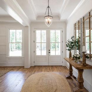 Réalisation d'une porte d'entrée champêtre avec un mur blanc, un sol en bois brun, une porte double, une porte en verre et un sol marron.