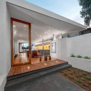 Exempel på en mellanstor modern ingång och ytterdörr, med vita väggar, mellanmörkt trägolv, en enkeldörr, glasdörr och brunt golv