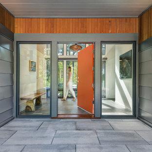 Example of a trendy gray floor entryway design in Boston with an orange front door