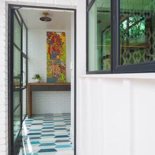 Example of a mid-sized minimalist blue floor single front door design in Austin with white walls and a glass front door